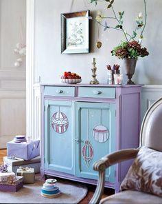 Un meuble dont les portes sont décorées de boules de noël en clous de tapissier, rehaussées de peinture et paillettes