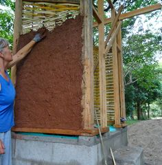 Nancy Bernstein, a carpenter and timber-framer from New York, daubing the wall of the the first composting toilet in Sabana Grande.
