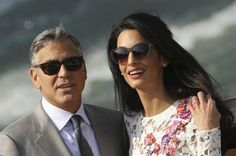 U.S. actor George Clooney and his wife Amal Alamuddin travel on a water taxi at the Grand Canal in Venice September 28, 2014.  REUTERS/Alessandro Bianchi