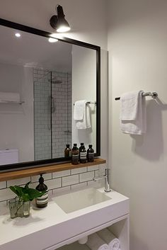 basement bathroom. I like the shelf under the mirror and the all white but black mirror frame look. clean.