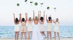 Bride and bridesmaids practice their bouquet toss on the beach! Bridesmaids chose their own mismatched knee length dresses in ivory and cream. | Palace Resorts Weddings ®