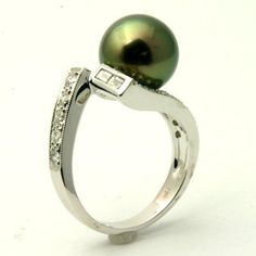 Cultured Black Pearl Engagement Ring - Elegance comes to mind when you first glance at this magnificent Cultured Black Pearl Engagement Ring that's stamped in a beautiful 18k White Gold featuring a high luster Tahitian Pearl set on the top of the unique cultured ring surrounded by White Baguette accent stones on the asymmetrically designed shank. This Black Pearl ring is 11.1mm in diameter & the total gem weight is equal to .57 carats. #unusualengagementrings