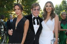 Show-stopping: While Victoria was sure to turn heads, actress and philanthropist Elizabeth Hurley looked equally stunning in a show-stopping wraparound white gown which highlighted her statuesque frame White Gowns, White Dress, David Furnish, Foundation Brands, Elton John Aids Foundation, Elizabeth Hurley, Gq Magazine, Victoria Beckham, Front Row