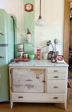 Big Chill fridge and vintage kitchen kitsch: Love that an old Hoosier style cabinet base is being utilized here.
