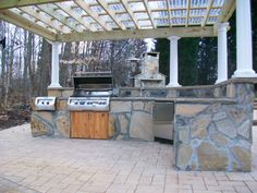 This pergola covered patio features an outdoor kitchen that any grillmaster would love.