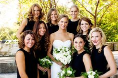 A gorgeous bride in an ivory strapless dress with a sweetheart neckline poses with her bridesmaids. The girls wear simple black sheath dresses to complement the wedding's rustic-chic style. They all carry white roses and carnations dressed with bright greenery. The John Parker Band played for the couple's outdoor wedding and reception, held at the Galleria Marchetti in Chicago.