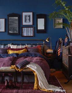 Fall bedroom in deep blue, maroon and mustard.