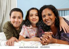 Family laying down together in a bed