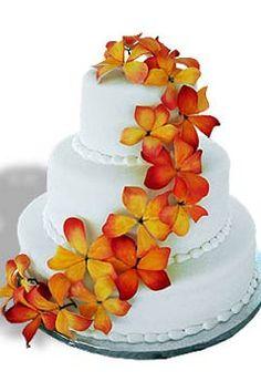 Three tier round fondant wedding cake design decorated with orange tropical Hawaiian flowers