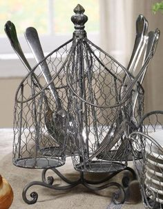 """Wire Utensil Holder, 7x7, SILVER by Home Decorators Collection. $19.00. 9.75""""H x 7.25"""" diameter.. This kitchen decor exudes vintage, rustic style with its wire design and aged finish. Perfect for keeping a few flatware and cutlery pieces handy at the dining table or on your kitchen countertop, this piece of home decor will free up your drawer space while adding a sophisticated touch to your kitchen decor. Place your order today. Quality crafted of metal for years of last..."""