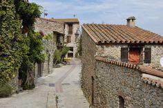 Uma rua estreita, entre construções de pedras, na antiga vila catalã de Castelnou, localizada no departamento dos Pirineus Orientais, região de Occitania, França.  Fundada no século X, é cercada por uma muralha, 8 torres e 4 portas.  Fotografia: Doronenko.