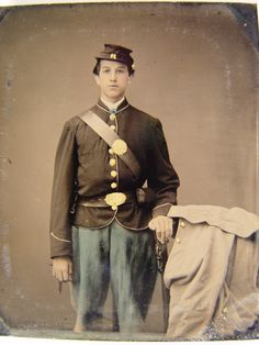 Unidentified young soldier in Union uniform next to chair draped with overcoat.