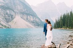 Bride and groom embracing on rock at Moraine Lake during their Banff Alberta Wedding