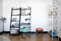 The dining room doubles as a workspace, with a small desk built into the leaning bookshelf.