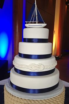 Nautical Wedding cake. 4 tier cake covered in white fondant with navy blue satin ribbon. Fondant rope knot wrapped around 2nd tier