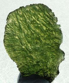 Moldavite  This Moldavite is a tectite that was created during a meteorite impact in the Czech Replublic.  Tectites are glass that is created during a meteorite impact. The energy of the impact turned sand into glass and it cooled down and solidified while it was flying through the air. This is a relatively large specimen, measuring ~5.5 x 3.5cm.