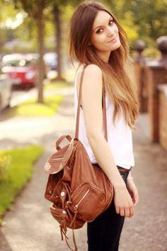 Acheter la tenue sur Lookastic:  https://lookastic.fr/mode-femme/tenues/debardeur-blanc-jean-skinny-noir-sac-a-dos-brun-ceinture/11248  — Débardeur blanc  — Sac à dos en cuir brun  — Ceinture en cuir tressée brune  — Jean skinny noir