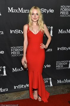 Playing with fire! Dakota Fanning sizzled in a low-cut ruby red dress at…