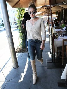 Gigi Hadid wears a lace-up sweater, choker, skinny jeans, round sunglasses, and thigh-high boots