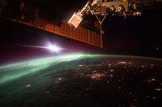 Aurora in early morning on Earth's horizon with city lights below and space station solar arrays above