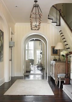 "Traditional Foyer with archway. Foyer. Beautiful foyer with archways and rustic dark hardwood floors.  Floors are 8""-10"" wide antique heart pine plank wood floors, dark stained and scraped.  Ceiling paint color: Benjamin Moore Cloud White CC-40.  Lighting: Most lighting used in this home are antique finds. T.S. Adams Studio. Interiors by Mary McWilliams from Mary Mac & Co."