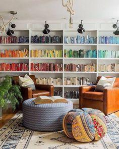 Fauteuils en cuir et livres triés par couleurs dans le coin lecture