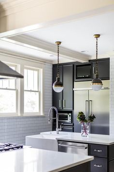 Contemporary dark gray kitchen boasts Small Hicks Pendants hung over a dark gray island contrasted with a honed white quartz countertop fitted with a farmhouse sink with a stainless steel pull down faucet and fixed over a stainless steel dishwasher positioned beside dark gray drawers adorning polished nickel pulls.