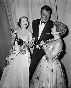 "John Wayne shows the gold statuettes he accepted for Gary Cooper and John Ford to two former Academy Award winners, Olivia De Havilland and Janet Gaynor after the ceremony in Hollywood March 19, 1953. Cooper won his Oscar as best actor, in ""High Noon."" and Ford as best director. Neither was in town for the presentations. Miss Gaynor was handed the first Oscar ever presented to an actress 25 years ago. (AP Photo)"