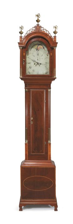 Federal inlaid mahogany tall case clock -  early 19th century -  Fretted, arched hood above conforming door opening to a painted metal face with moon phase enclosed by columnettes with brass stop fluting, the case with inlaid door, flanked by fluted corner columns with brass stops, inlaid plinth, bracket feet.   H: 108 in.
