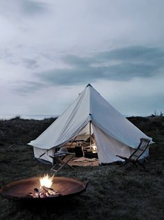 A tall, roomy tent loaded with camping gear, a chair, and a safe campfire. What's not to like with this camping scenario?