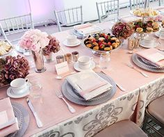 Layers of soft pink and silvery grey combine for a classically chic table covered in delicious sandwiches and sweets.