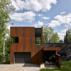 Montreal architect Paul Bernier has completed a blackened timber and weathering steel-clad cabin on the shores of a lake in rural Quebec.