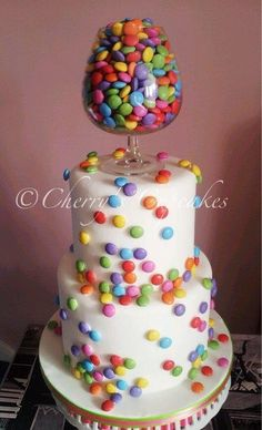 Double tiered wedding cake covered in chocolate candy, with a goblet full on top!