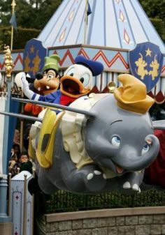 Donald and Goofy ride the Dumbo ride at Disneyland