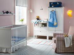 Vauvanhuone, jossa valkoiset pinnasänky, hoitopöytä ja vaatekaappi sekä puna-beige nojatuoli.