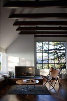 暖炉に、花に、木立ちに、簡素で座り心地のよいソファが、調和よく。木のテーブルと床は、磨き込まれてすがすがしいつやを放っています。