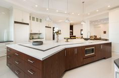 A modern kitchen with a slightly curving island and three pendant lights hanging above. Source: https://www.zillow.com/digs/Home-Stratosphere-boards/Luxury-Kitchens/