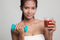 healthy asian woman with dumbbell and tomato juice
