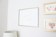 a simple coral, mint & gold nursery with baby's name in framed calligraphy art