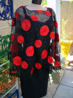 The dressiest of the ponchos:  sheer black mesh with red satin flowers, black sequins and lace trim (the production quantity has a black satin neckline).