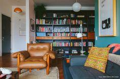 Sala de estar com estante preta ao fundo e poltrona Mole do designer Sérgio Rodrigues.