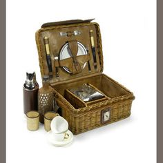 An early leather and wicker cased picnic set, British, circa 1905, the basket with lid opening to reveal fitted interior, complete with early Thermos flask, two Mintons cups, two wicker covered glasses, saucers, plates and cutlery housed in leather straps inside lid, fine wicker drinks flask, and two glasses in separate wicker container, the basket 15½in wide, a great compact picnic set for a veteran car.