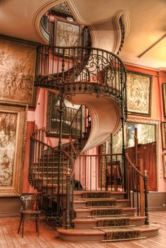 I love this combination of the spiral staircase and the huge pictures
