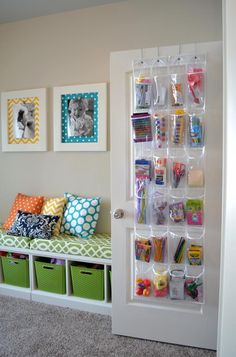 a fancy plastic pocket to store toys hanging in the white wodoen door in the nursery with green patterned desk and rattan moses basket
