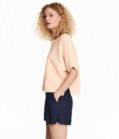 Hellapricot. Weiter Pullover in Strukturstrick aus Baumwollmischung. Modell mit weitem Halsausschnitt, kurzen Fledermausärmeln und seitlichen Schlitzen.