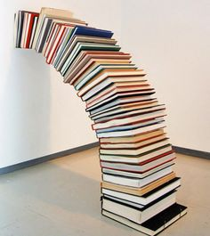 Pie de Amigo (2010) by Miler Lagos (milerlagos.com). A pencil is placed just inside the covers of these architecture books, allowing the curved stack to maintain its lean against the wall. [ #books #installation #sculpture ]