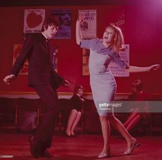 Sixties Fashion - A young mod style couple dance together in a London nightclub circa 1965.