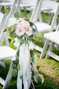 small posies with white and yellow flowers tied with blue and white striped ribbon to aisle chairs