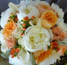 Beautiful summer bridal bouquet of White Peonies, Peach Garden Roses, Miniature Calla Lilies, Pink Spray Roses, Hypericum Berries, Dusty Miller, and Italian Ruscus   Walden Floral Design