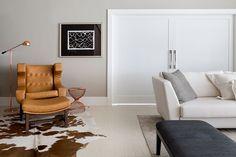 Parede cinza, poltrona com design criativo e sofá branco.